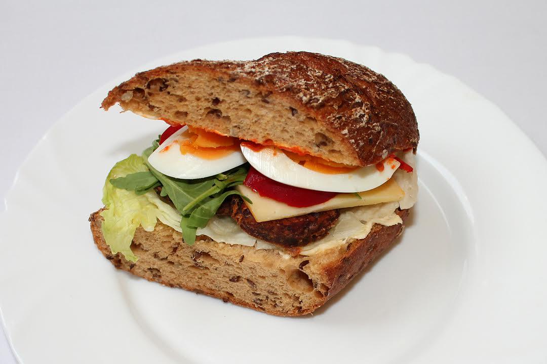 Helyben sütött gluténmentes zsömléből, laktózmentes vajból, zöldségkrémből, salátából, chedar sajtból, öko gazdaságból származó bivaly szalámiból készült egészséges szenvics