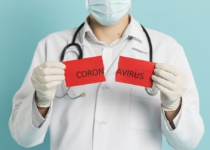 front view doctor with medical mask holding up torn paper with coronavirus 23 2148445065