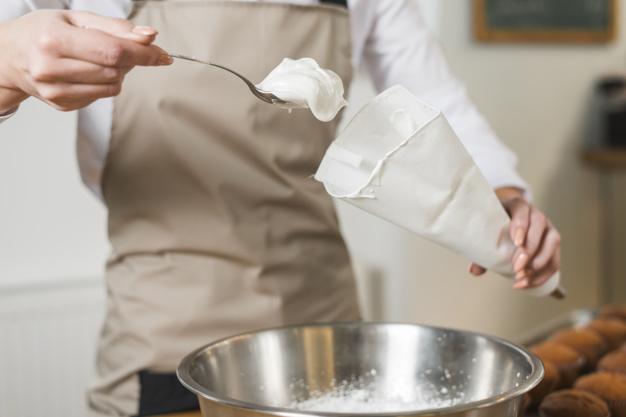 female baker filling whipped cream white icing bag 23 2148028100